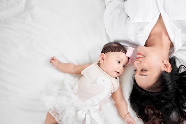 Schattig klein babymeisje en haar moeder liggend op een vloer.