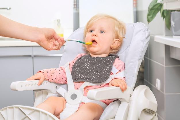 Schattig klein babymeisje in een keuken