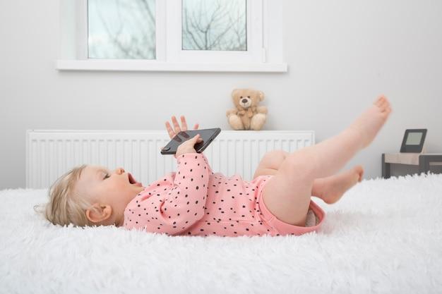 Schattig klein babymeisje met smartphone in ouder slaapkamer.