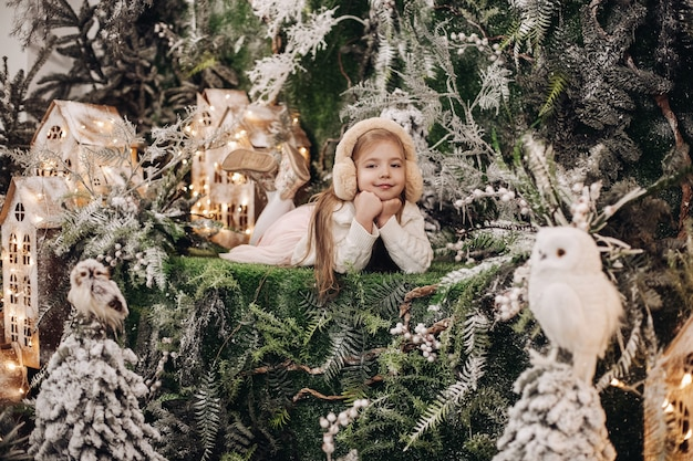 Schattig klein blank kind in beige oorkappen met kin op handen omringd door kerstversieringen en glimlachend winter wonderland concept.