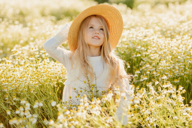 Schattig klein blond meisje in een katoenen jurk en strohoed loopt in een veld met madeliefjes en verzamelt ze in de mand