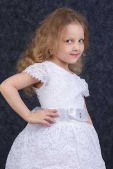 Schattig klein blond meisje in een mooie witte jurk op een donkere achtergrond. zes jaar oud mooi meisje
