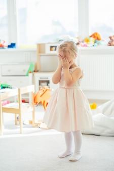 Schattig klein blond meisje in een roze jurk die haar gezicht achter haar handen verbergt.