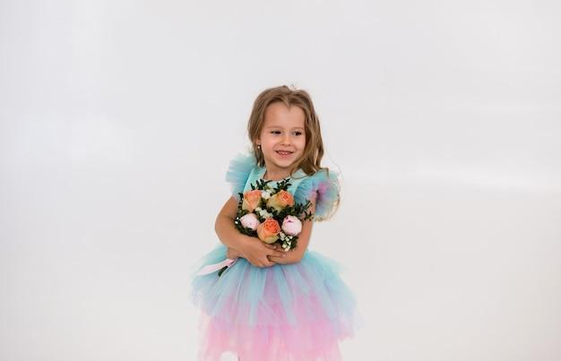 Schattig klein blond meisje in een tule jurk staat en houdt een boeket verse bloemen op een witte achtergrond met een kopie van de ruimte