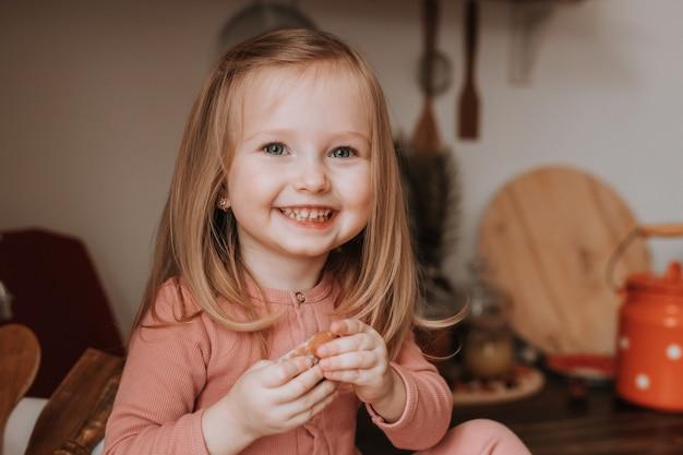 Schattig klein blond meisje in roze pyjama koekjes eten in de keuken gezonde snack voor kinderen