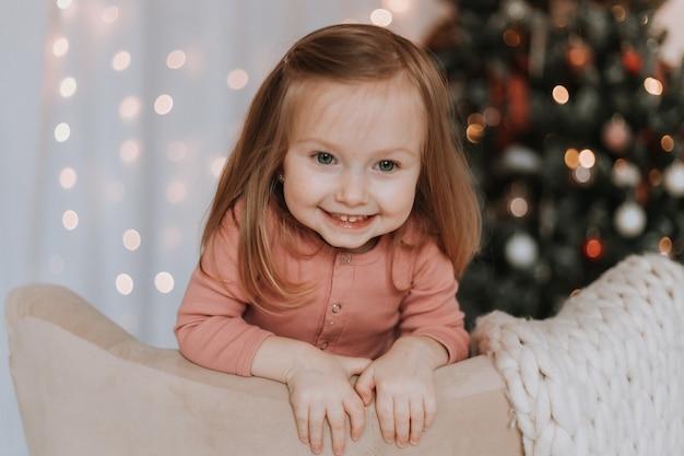 Schattig klein blond meisje knielt in een stoel tegen de achtergrond van een kerstboom