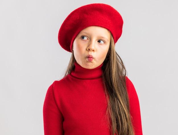 Schattig klein blond meisje met rode baret op zoek naar kant geïsoleerd op een witte muur met kopieerruimte