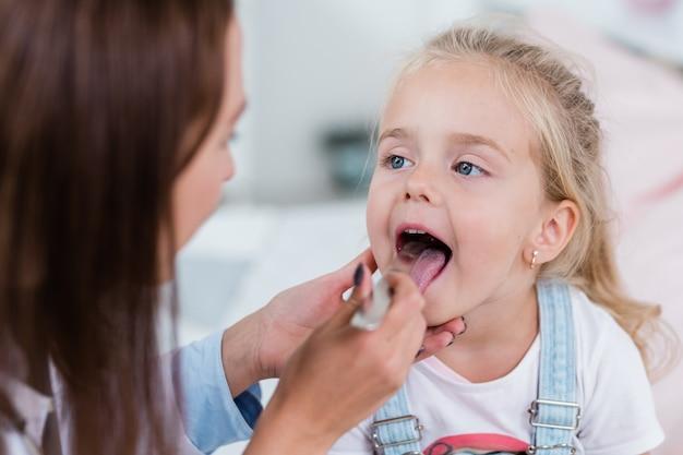 Schattig klein blond meisje mond openen zittend voor clinicus haar keel met stell spatel te onderzoeken