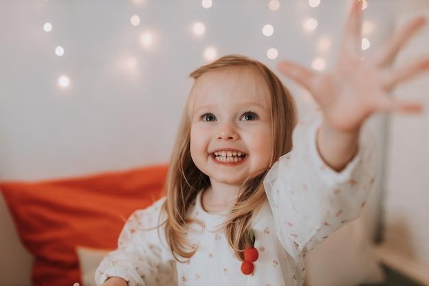 Schattig klein blond meisje strekte haar hand uit voor een kerstcadeau producten voor kinderen