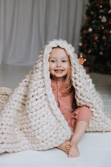 Schattig klein blond meisje zit gewikkeld in een lichte plaid van groot breiwerk bij de kerstboom