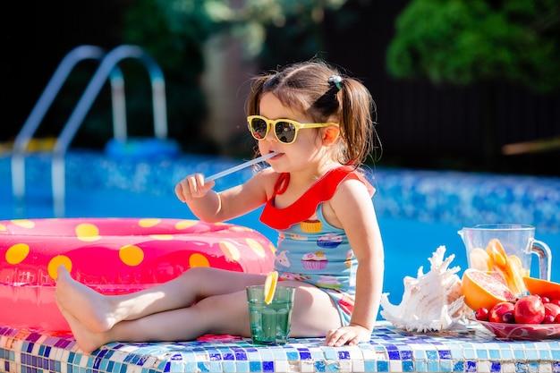 Schattig klein brunette meisje in zonnebril en zwembroek drinkt limonade bij het zwembad.