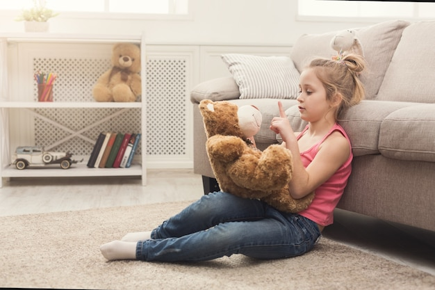 Schattig klein casual meisje omhelst teddybeer. mooi kind dat thuis speelt, zittend op de vloer in de buurt van de bank met haar favoriete speeltje, kopieer ruimte