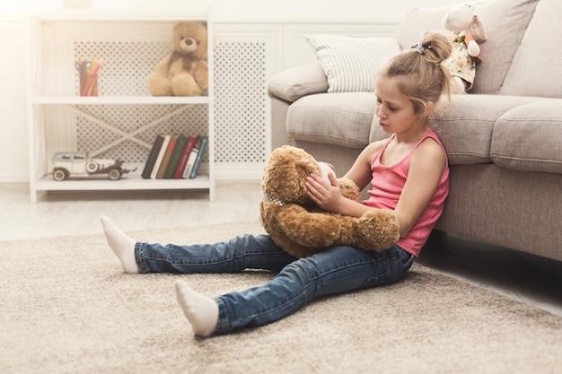 Schattig klein casual meisje omhelst teddybeer. verdrietig kind dat thuis speelt, zittend op de vloer in de buurt van de bank met haar favoriete speeltje, kopieer ruimte