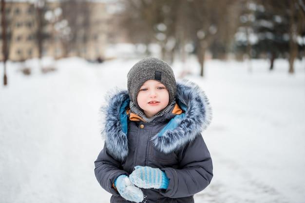 Schattig klein grappig kind in kleurrijke winterkleren plezier met sneeuw,