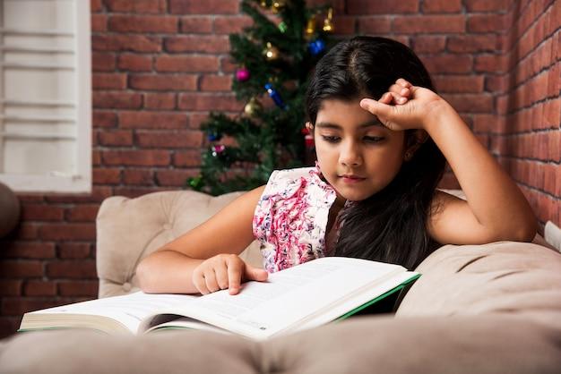 Schattig klein indiaas aziatisch meisje dat een boek leest terwijl ze thuis op de bank of op de bank zit