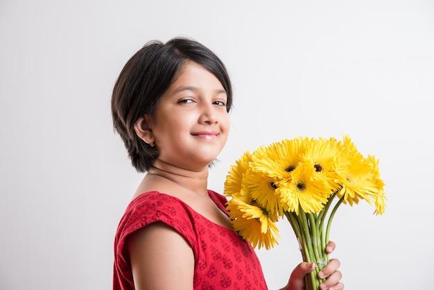 Schattig klein indiaas meisje met een bos of boeket verse gele gerbera-bloemen. geïsoleerd op witte achtergrond