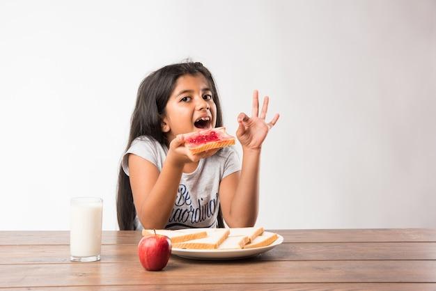 Schattig klein indiaas of aziatisch klein meisje aan het ontbijt. tafel vol sneetjes brood met jam, glas melk, verse appel en gekookt ei