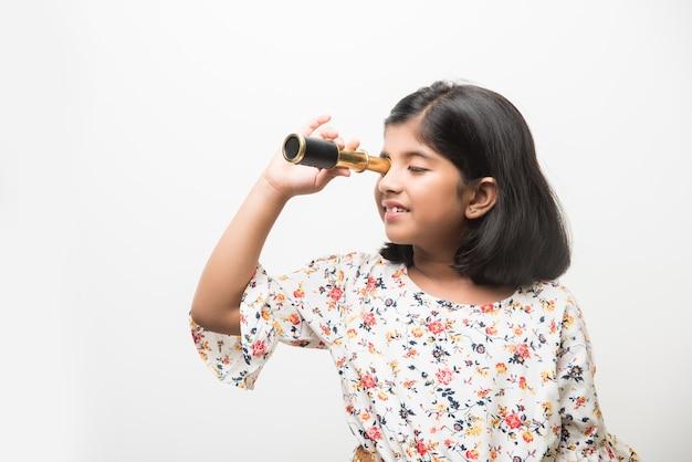 Schattig klein indiaas of aziatisch meisje dat een rektelescoop gebruikt en omhoog kijkt, wil een wetenschapper worden. staande geïsoleerd over witte of groene schoolbordachtergrond