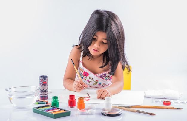 Schattig klein indiaas of aziatisch meisje dat geniet van schilderen thuis met papier, waterverf en kunstpenseel. selectieve focus