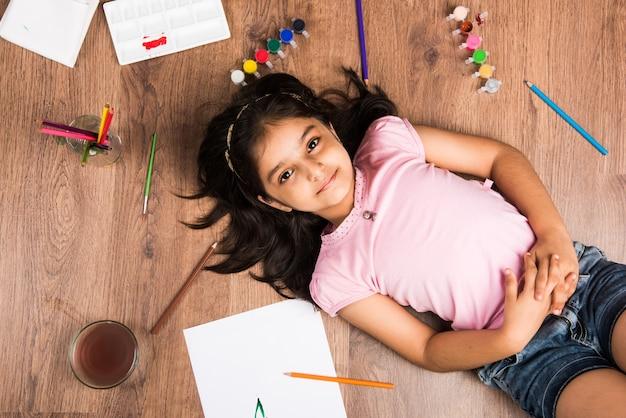 Schattig klein indiaas of aziatisch meisje dat kleurt, tekent of schildert met kleuren, potloden enz.
