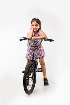 Schattig klein indiaas of aziatisch meisje dat op de fiets rijdt, geïsoleerd op een witte achtergrond met ballonnen