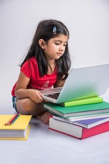 Schattig klein indiaas of aziatisch meisje dat op laptop studeert of aan een schoolproject werkt terwijl liggend of zittend op de vloer, geïsoleerd op witte achtergrond