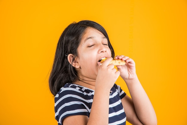 Schattig klein indiaas of aziatisch meisje dat smakelijke hamburger, sandwich of pizza eet in een bord of doos. staande geïsoleerd over blauwe of gele achtergrond.