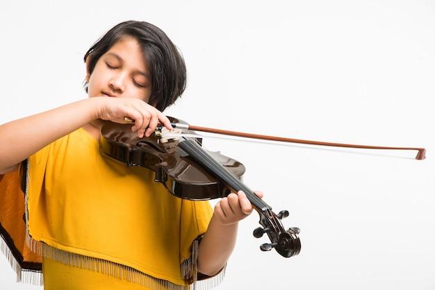 Schattig klein indiaas of aziatisch meisje dat viool speelt, geïsoleerd op witte achtergrond