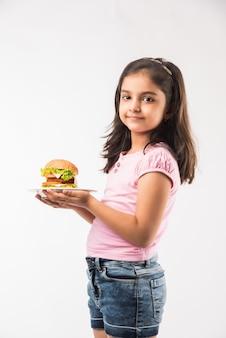 Schattig klein indiase of aziatische meisje hamburger eten op witte achtergrond
