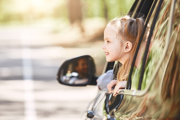 Schattig klein kaukasisch meisje dat in de auto zit en uit het raam kijkt, familieweg