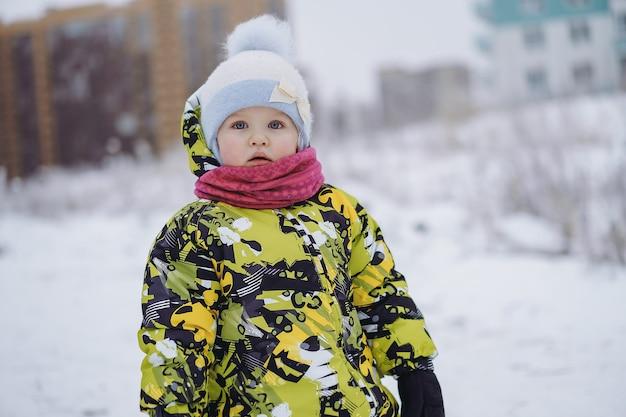 Schattig klein kaukasisch meisje in gele overall en op winterdag in park