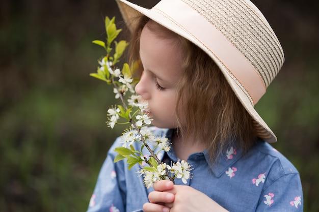 Schattig klein kaukasisch meisje van 5 jaar oud dat de geur van kersenbloemen inademt in een park dat onder een bloeiende kersenboom staat