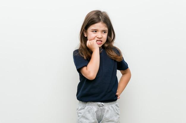 Schattig klein kaukasisch meisje vingernagels bijten, nerveus en erg angstig.