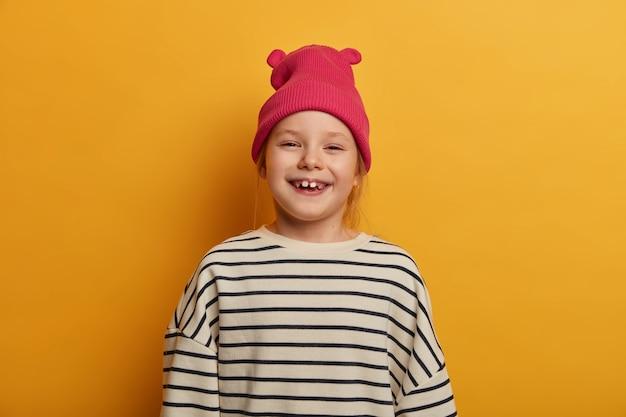 Schattig klein kind giechelt positief heeft ontbrekende tanden, voelt zich vrolijk, verheugt zich op mooie dag, draagt roze modieuze hoed en gestreepte losse trui, poseert tegen gele muur, maakt gedenkwaardige foto