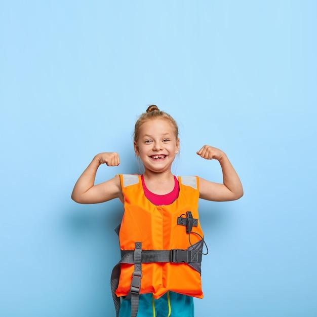 Schattig klein kind heft armen op en toont spieren, draagt oranje opgeblazen reddingsvest