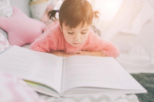 Schattig klein kind meisje leest thuis een boek. grappig mooi kind plezier in kinderkamer.