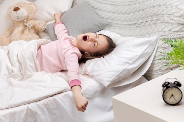 Schattig klein kind meisje wordt wakker uit de slaap