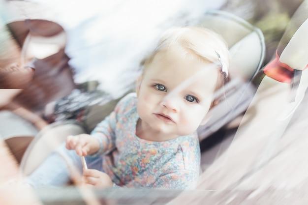 Schattig klein kind meisje, zittend in een veiligheidsstoel in de auto. gevaar preventie.