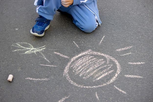 Schattig klein kind tekent de zon met krijt buitenshuis