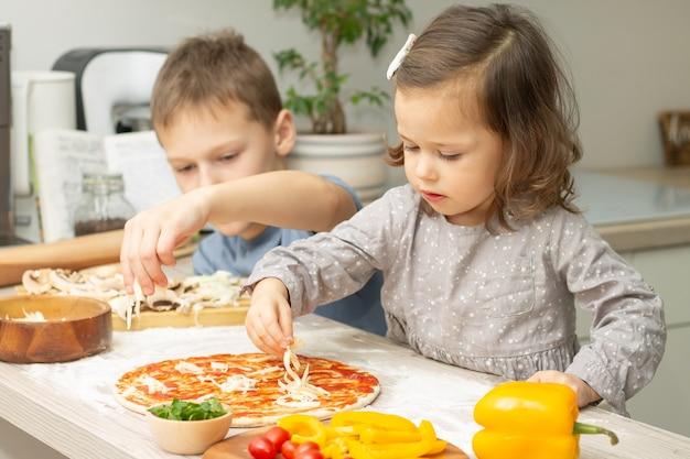 Schattig klein meisje 2-4 in grijze jurk en jongen 7-10 in t-shirt pizza samen koken in de keuken. broer en zus koken