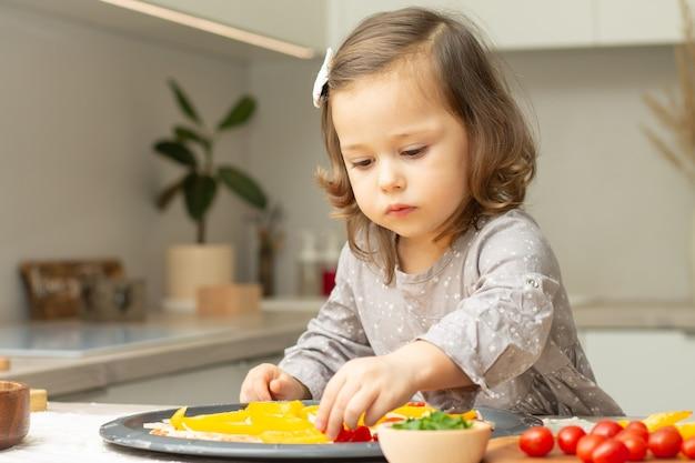 Schattig klein meisje 2-4 in grijze jurk pizza in de keuken koken. kid schikt ingrediënten op pizzabodem