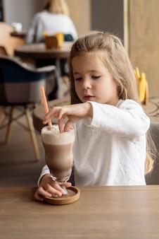 Schattig klein meisje 5 jaar oud drinkt cacao in een café