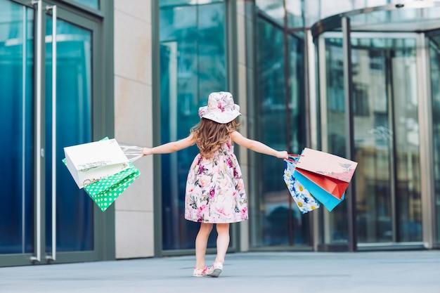 Schattig klein meisje bij het winkelen. portret van een kind met boodschappentassen. boodschappen doen. meisje.
