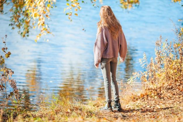 Schattig klein meisje buiten op herfstdag wandelen in de buurt van meer