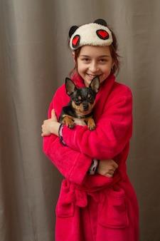 Schattig klein meisje chihuahua pup staande houden en kijken. meisje met chihuahua honden in haar armen. meisje van 9 jaar oud met een huisdier thuis in haar armen. het concept van liefde voor dieren. huis