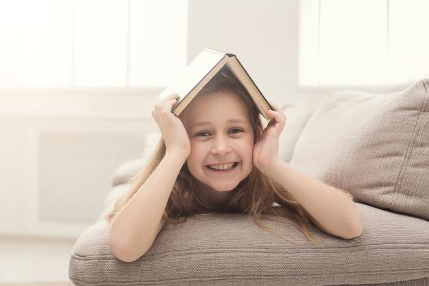 Schattig klein meisje dat een boek leest terwijl ze thuis op de bank ligt. onderwijs en vrije tijd concept, kopieer ruimte
