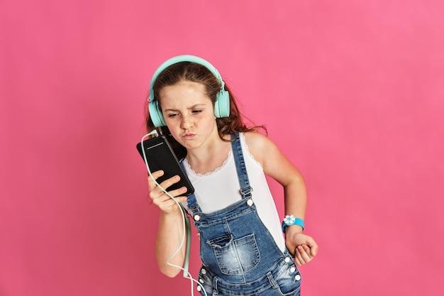 Schattig klein meisje dat naar muziek luistert met een telefoon en koptelefoon op een roze muur