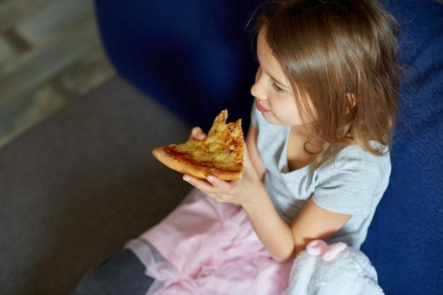 Schattig klein meisje dat op de bank zit en thuis een stuk italiaanse pizza eet, lekkere maaltijd