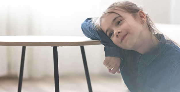 Schattig klein meisje dat op de tafel leunt en in de verte kijkt, terug naar schoolconcept.