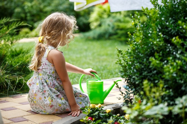 Schattig klein meisje dat planten in de tuin water geeft.